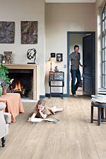 Parquet laminado de roble medio im 1856 de la marca quick-step de la serie impressive  en un ambiente de habitación.
