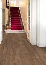 Parquet laminado de roble barnizado natural de la marca quick-step de la serie largo en un ambiente de habitación.