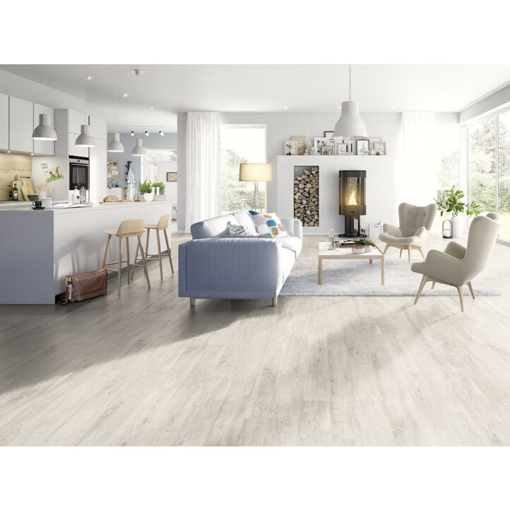 Un suelo laminado armonioso de Egger Home, el EHL129 Castaño Piagola blanco, instalado en la sala de estar.