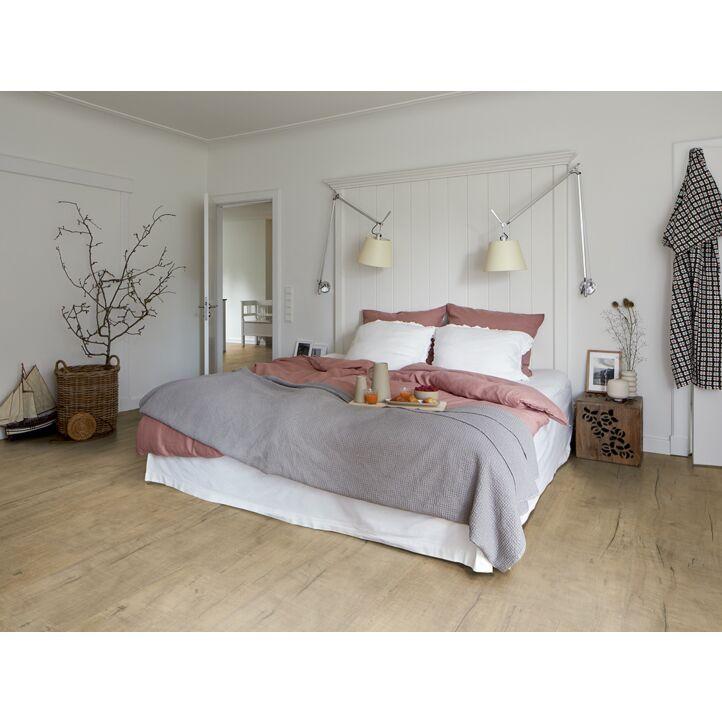 Un suelo laminado armonioso de Egger Home, el EHL171 Roble Springfield Natural, instalado en la sala de estar.