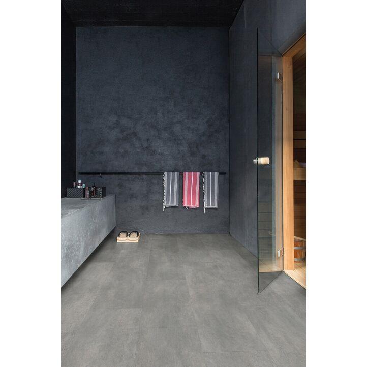 Parquet vinílico de la marca Quick-Step livyn hormigón gris oscuro AMCP40051 de la serie Ambient Click Plus en un ambiente de habitación.