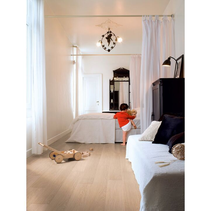 Parquet laminado de roble barnizado blanco de la marca quick-step de la serie impressive  en un ambiente de habitación.