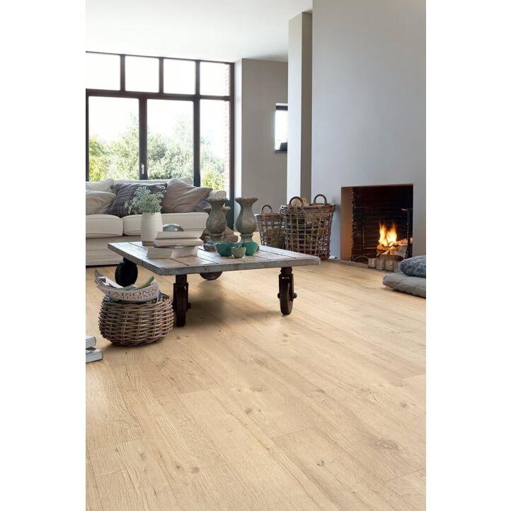 Parquet laminado de roble tratado con chorro de arena natural de la marca quick-step de la serie impressive en un ambiente de habitación.