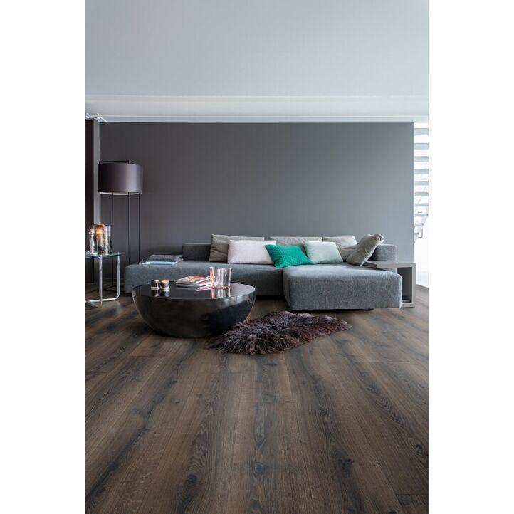 Parquet laminado de roble desierto marrón oscuro cepillado de la marca quick-step de la serie majestic en un ambiente de habitación.