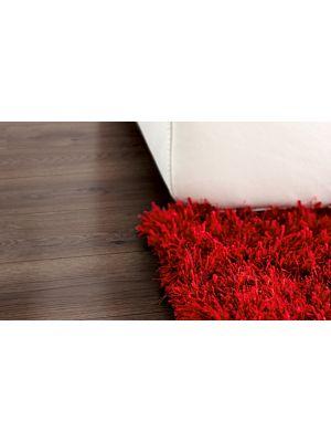 Parquet laminado de la marca pergo de la gama living expression roble chocolate serie L0323-01754  en un ambiente de habitación.