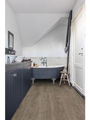 Parquet laminado de roble bosque gris claro mj3547 de la marca quick-step de la serie majestic en un ambiente de habitación.