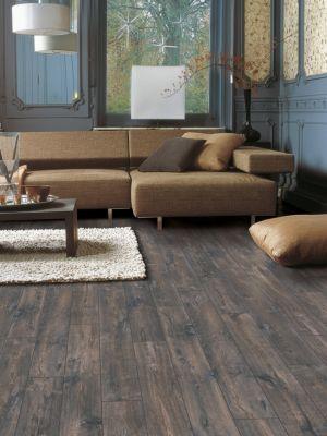 Parquet laminado de roble marrón mejorado de la marca quick-step de la serie eligna wide en un ambiente de habitación.