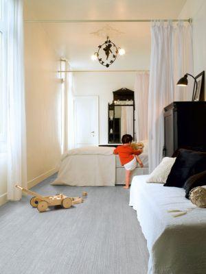 Parquet laminado de roble caribeño gris de la marca quick-step de la serie perspective wide en un ambiente de habitación.
