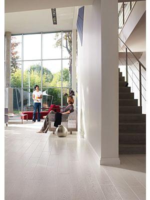 Parquet laminado de pino blanco cepillado de la marca quick-step de la serie perspective en un ambiente de habitación