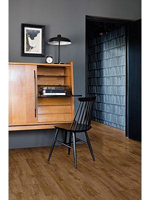 Parquet vinílico de la marca Quick-Step livyn Roble otoño miel PUCP40088 de la serie Pulse Click Plus en un ambiente de habitación con personas.