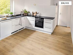 Suelo laminado Roble Brook Miel de la marca Egger Home con código EHL103 instalado en una cocina reluciente.
