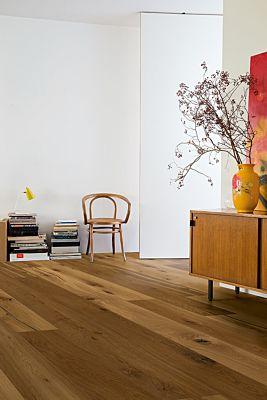 Parquet laminado de roble marrón café mate de la marca quick-step de la serie castello en un ambiente de habitación.