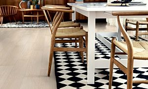 parquet laminado roble danés moderno de la marca pergo de la serie living expression sensation resistente al agua superficialmente l0331-03372 en un ambiente de habitación con una alfombra.