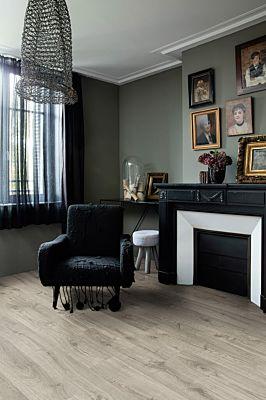 Parquet vinílico de la marca Quick-Step livyn Roble otoño miel PUCL40088 de la serie Pulse Click en un ambiente de habitación con personas.