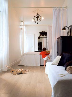Parquet laminado de planchas quemadas de la marca quick-step de la serie impressive ultra en un ambiente de habitación.