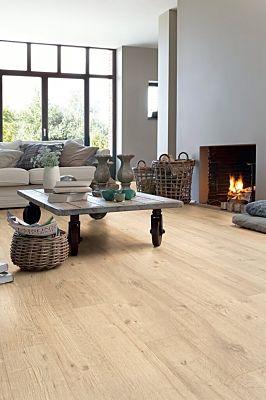 Parquet laminado de roble tratado con chorro de arena natural de la marca quick-step de la serie impressive ultra en un ambiente de habitación.