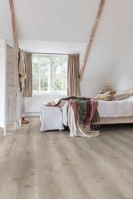 Parquet laminado de roble desierto cálido natural de la marca quick-step de la serie majestic en un ambiente de habitación.