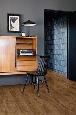 Parquet vinílico de la marca Quick-Step livyn Roble otoño gris claro PUCL40089 de la serie Pulse Click en un ambiente de habitación con personas.
