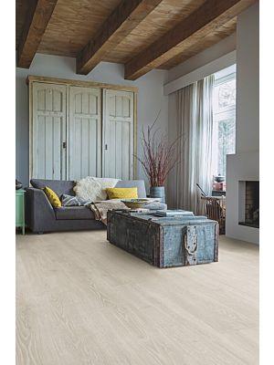 Parquet laminado de roble bosque natural mj3546 de la marca quick-step de la serie majestic en un ambiente de habitación.