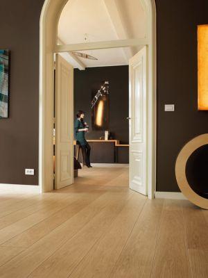 Parquet laminado de roble cambridge natural de la marca quick-step de la serie largo en un ambiente de habitación.