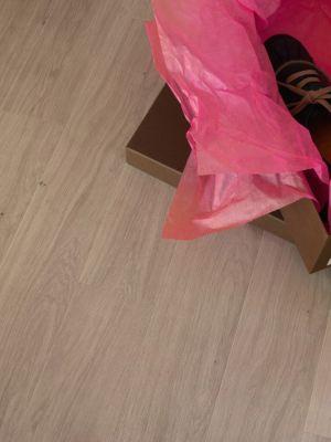 Parquet laminado de roble barnizado gris claro de la marca quick-step de la serie perspective en un ambiente de habitación.